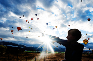 2018 Albuquerque Balloon Fiesta | Jude pointing to balloons with sun flare | Lyndsay Stradtner | Life In Motion Photography | Family Travel Photographer