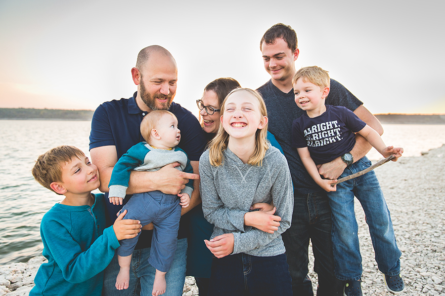 silly family picture of mom, dad and 5 kids standing on rocky lake shore with lake in background | Life In Motion Photography