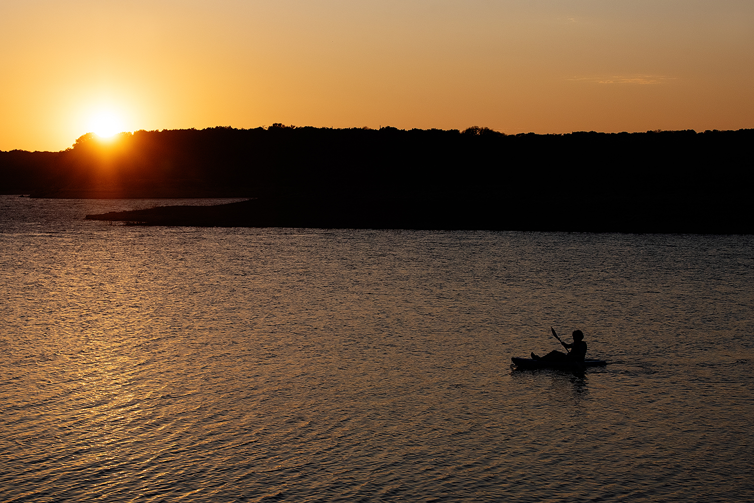 sunset photo of boy in kayak