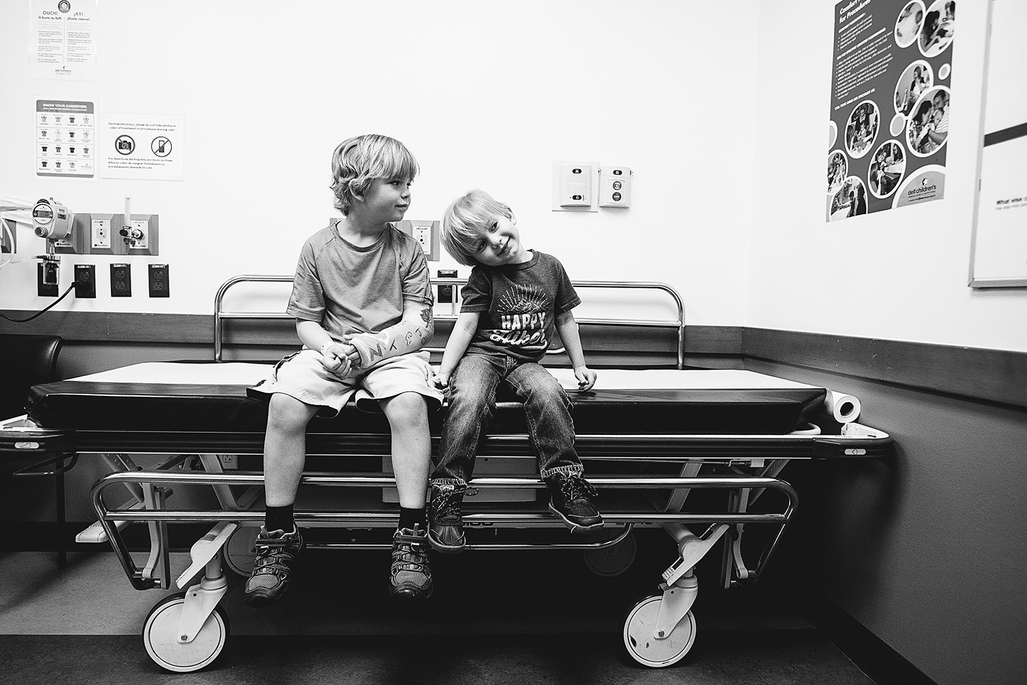 photo of boys sitting in hospital room on bed