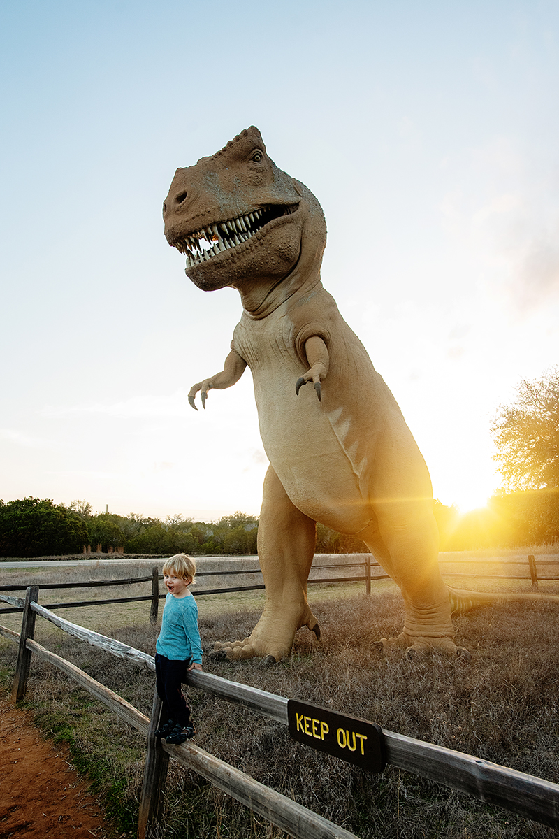 photo of zachary and large dinosaur statue at sunset