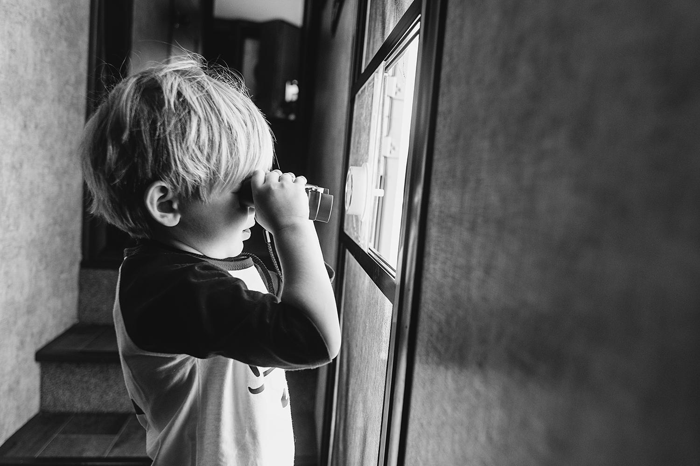 Photo of zachary using binoculars at front door of RV