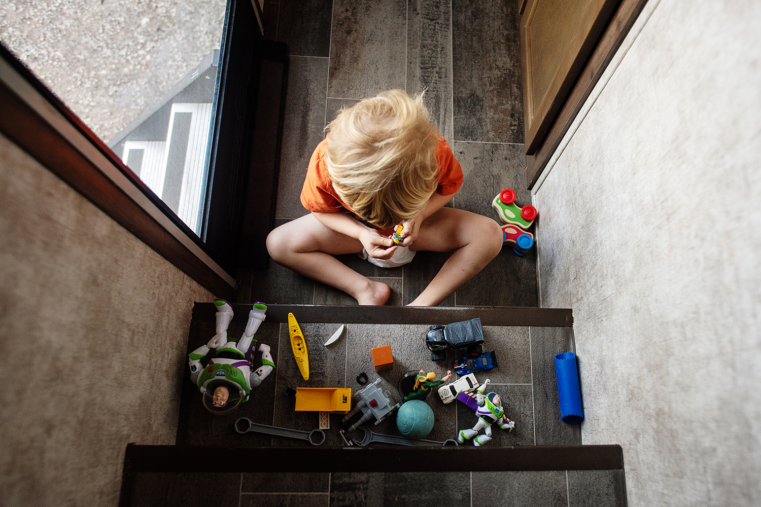 photo of zachary playing with toys on steps